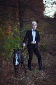 foto of greyhounds  - Young attractive man in suit and tie with a greyhound dog in autumn outdoors - JPG
