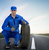 image of towing  - Young Smiling mechanic showing thumbs up next  car tires  - JPG