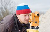 stock photo of cartographer  - Engineer at the construction site makes measurements with leveling - JPG