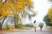 foto of fall day  - Young mother with her little daughter walking in fall park on yellow fallen leaves one autumn day - JPG