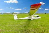 foto of glider  - Sailplane glider airplane wide angle shot on the ground field waiting for take-off.
