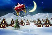 stock photo of santa sleigh  - Santa flying his sleigh against cute christmas village at night - JPG
