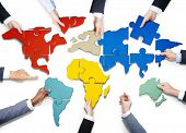 foto of jigsaw  - Group of Business People with Jigsaw Puzzle Forming in World Map - JPG
