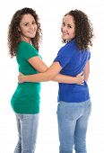 picture of identical twin girls  - Portrait of an isolated couple of real twin sisters over white wearing blue and green shirt - JPG