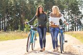 stock photo of girl walking away  - Two girls with bicycles in countryside looking away - JPG