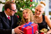 stock photo of boxing day  - Parents and daughter with Christmas gifts on boxing day  - JPG