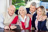 stock photo of family bonding  - Portrait of smiling senior woman using digital tablet with family at nursing home - JPG