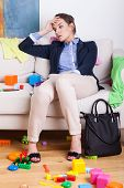 stock photo of superwoman  - Tired young mother sitting on sofa after hard day at work - JPG