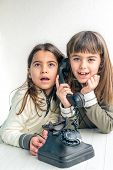 stock photo of 7-year-old  - Seven year old girl talking on the old vintage phone and her sister eavesdropping her conversation. White background.
