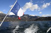 stock photo of annecy  - Annecy Lake and mountains from boat and French flag