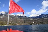 pic of annecy  - Annecy Lake and mountains from boat and red flag