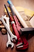 foto of pipe wrench  - Close up Hand Working Tools like Open Ended and Pipe Wrenches Cross Pein Sledge Hammer and a Pair of Gloves on Top of a Wooden Table - JPG