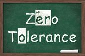 stock photo of zero  - Zero Tolerance Zero Tolerance written on a chalkboard with letters from the periodic table and a piece of white chalk - JPG