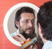 stock photo of beard  - Bearded man trim his beard with electric shaver - JPG