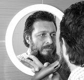 image of beard  - Bearded man trim his beard with electric shaver - JPG