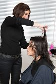 stock photo of hair cutting  - Happy woman cutting hair at the hairdresser salon - JPG