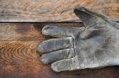 stock photo of dirty  - Old safety gloves on wooden background, Gloves on dirty works. ** Note: Soft Focus at 100%, best at smaller sizes - JPG
