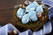 image of bird egg  - Happy Easter blue decoration eggs in birds nest on dark wood table background - JPG