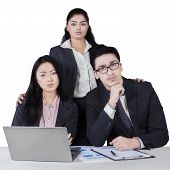 image of multicultural  - Three member of confident multicultural business team with laptop and paperwork isolated on white - JPG