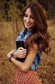 stock photo of auburn  - cute young woman with long auburn hair in the autumn forest reading a book - JPG