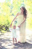 picture of mother baby nature  - Sunny photo mother and child walking barefoot in the forest mom helps the baby to take the first steps on a summer day - JPG
