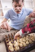 foto of grandfather  - Young boy is playing chess with his grandfather at home - JPG