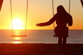 pic of swing  - Single or divorced woman alone missing a boyfriend while swinging on the beach at sunset - JPG