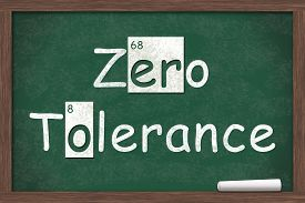 image of zero  - Zero Tolerance Zero Tolerance written on a chalkboard with letters from the periodic table and a piece of white chalk - JPG