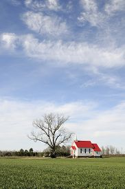 foto of red siding  - Wood siding church with red roof on sunny day with  beautiful sky - JPG