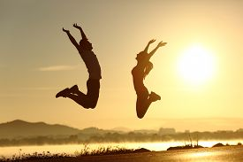 foto of jumping  - Fitness couple jumping happy at sunset with the sun in the background - JPG