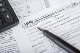 stock photo of time-saving  - Closeup of a pen pointing at tax form with calculator symbolizing the time to pay tax - JPG