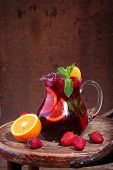 foto of jug  - Jug of wine of Sangrija on a wooden table with an orange and a strawberry - JPG