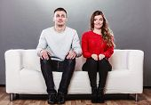 stock photo of couch  - Shy woman and man sitting on sofa couch next each other - JPG