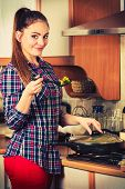 stock photo of stir fry  - Woman in kitchen cooking stir fry frozen vegetables and tasting. Girl frying making delicious risotto. Dinner food meal. ** Note: Soft Focus at 100%, best at smaller sizes - JPG