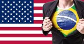 stock photo of brazilian money  - Businessman stretching suit with Brazilian flag on american flag background - JPG