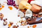 foto of dry fruit  - Cheeses with dried fruits and nuts on wooden board - JPG