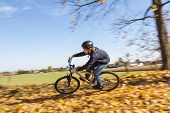 stock photo of dirt-bike  - boy jumps with his dirt bike over natural ramps in open area and enjoys racing  - JPG