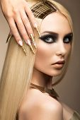 stock photo of nail-design  - Beautiful fashionable girl in a glamorous image with bright makeup and long gold nails - JPG
