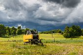 pic of combine  - Idle combine and dramatic storm cloud in the countryside - JPG