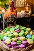 foto of roosters  - Multicolored macaroon in a wicker basket on the table with a figure of a rooster - JPG