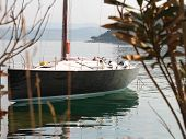 foto of mast  - Black Carbon shinning Sailboat with reflection in the sea surface - JPG