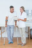 stock photo of crutch  - Doctor showing clipboard to her patient with crutch in medical office - JPG