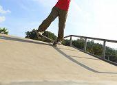 foto of skateboard  - closeup of skateboarder legs skateboarding at skatepark ramp - JPG