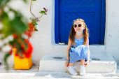 picture of greek-island  - Charming little girl at typical greek traditional village with white houses and colorful doors on Mykonos Island - JPG