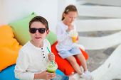stock photo of brother sister  - Two cute kids brother and sister drinking fresh smoothies on a colorful pillows at outdoor cafe on summer day - JPG