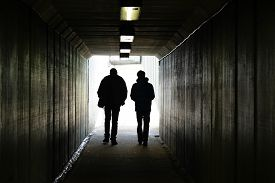 picture of girl walking away  - Two persons walk to the light in the end of the tunnel - JPG