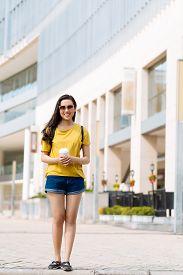 foto of takeaway  - Portrait of smiling girl with takeaway coffee outdoors - JPG