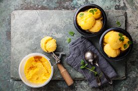 foto of mint leaf  - Mango ice cream sorbet with mint leaves in black bowls Spoon for ice cream and plastic container on stone slate background - JPG