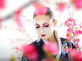 Artistic Portrait Of Japan Geisha Woman With Creative Make-up Near Sakura Tree