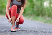 Running shoes - closeup of woman tying shoe laces. Female sport fitness runner getting ready for jog poster
